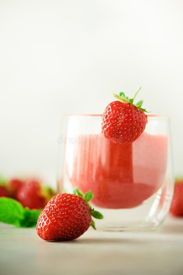 Gezonde aardbei smoothie in glas op grijze achtergrond met exemplaarruimte banner De zomervoedsel en schoon het eten concept royalty-vrije stock foto's