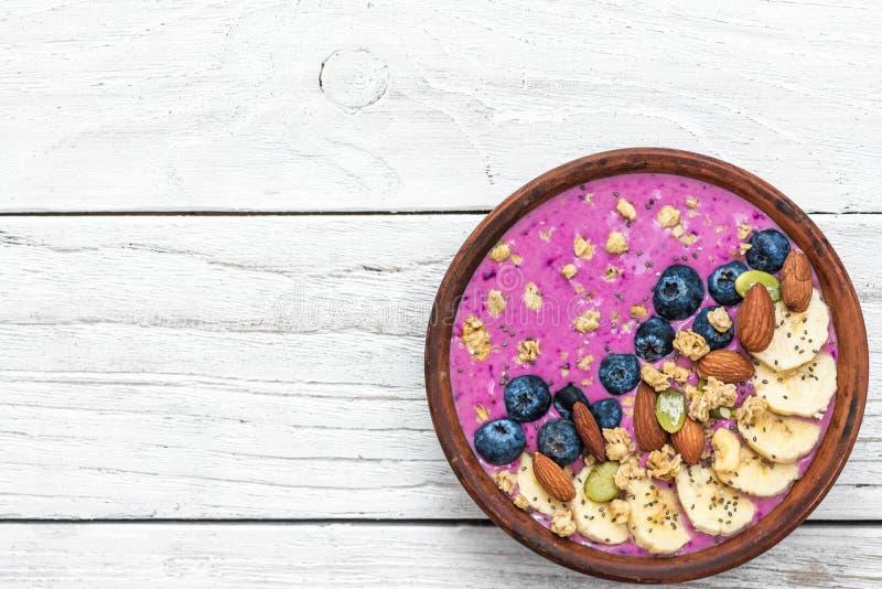 Gezonde acai van het veganistontbijt smoothie werpt met bosbes, vruchten, granola, amandelen, pompoen en chiazaden stock foto's