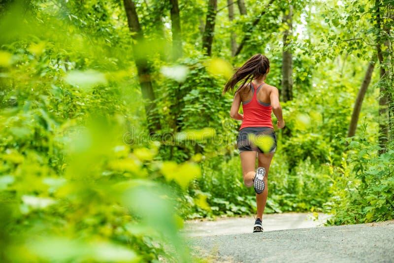 Gezonde actieve de agentjogging van de levensstijlvrouw in bos de atleet van de wegsport opleiding openlucht in groene aard Het g stock foto