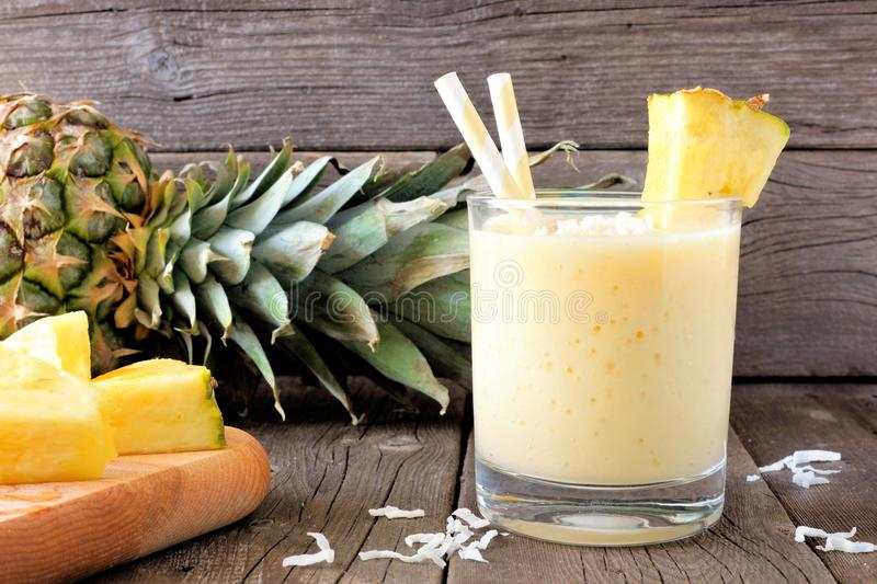 Gezonde ananas smoothie, scène tegen hout stock fotografie