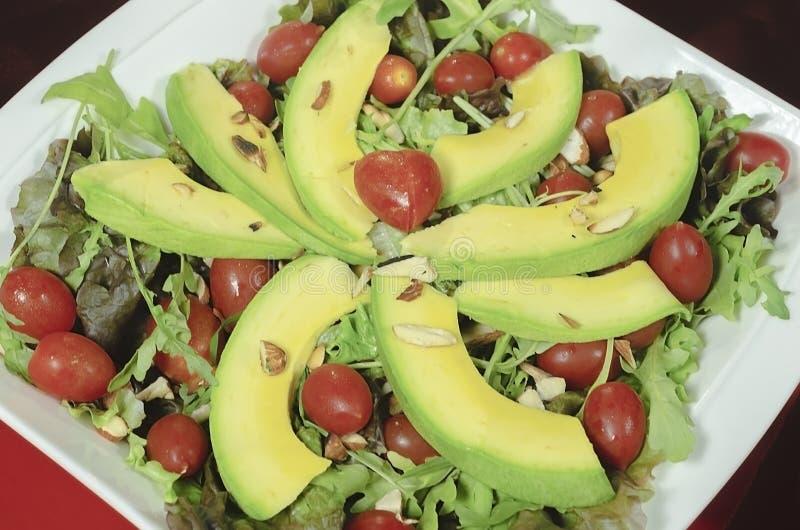 Gezonde avocadoschotel, kersentomaten, amandelsla en voor romantisch diner stock fotografie