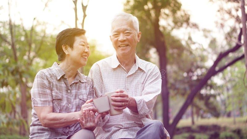 Gezonde Aziatische hogere paar het drinken koffie in ochtendpark toge stock afbeelding