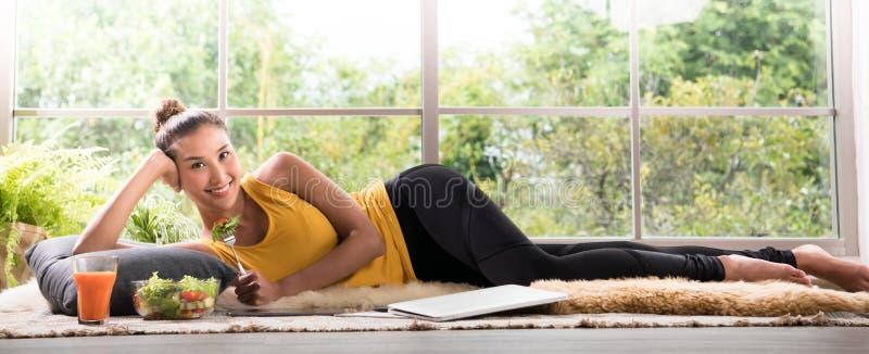 Gezonde Aziatische vrouw die op de vloer liggen die salade eten die ontspannen en comfortabel kijken stock fotografie