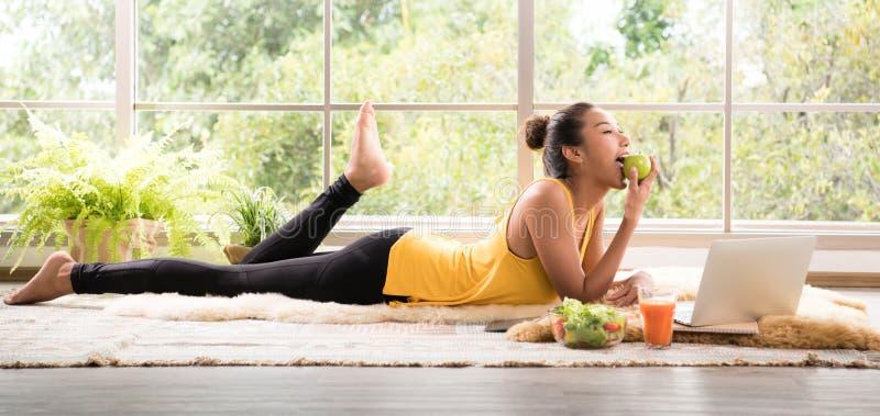 Gezonde Aziatische vrouw die op de vloer liggen die salade eten die ontspannen en comfortabel kijken stock afbeeldingen