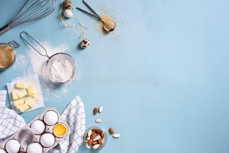 Gezonde bakselingrediënten - bloem, amandelnoten, boter, eieren, koekjes over een blauwe lijstachtergrond Bakkerij achtergrondkad stock foto's