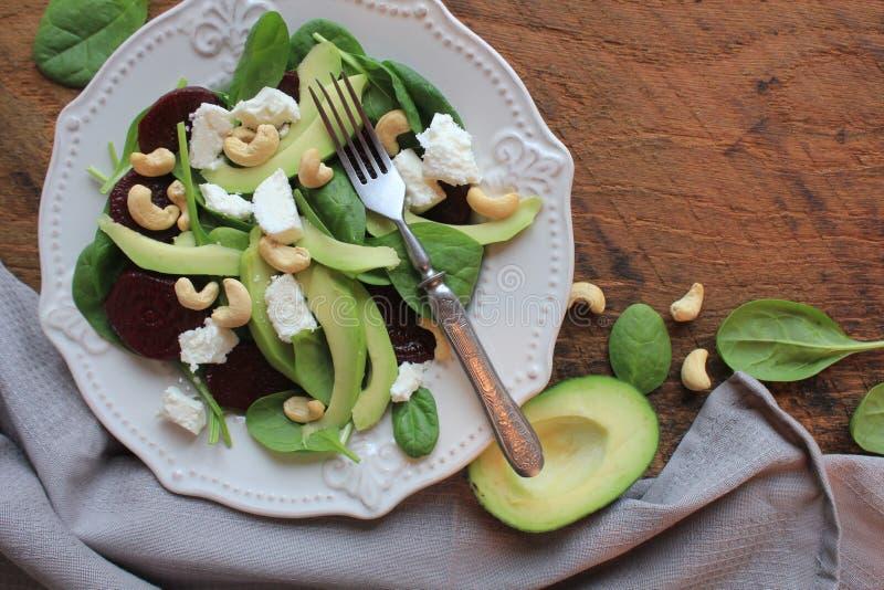 Gezonde bietensalade met verse zoete babyspinazie, noten, feta-kaas en avocado Plaat met salade op rustieke houten lijst royalty-vrije stock foto