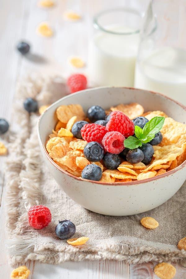 Gezonde cornflakes met bessen en melk op witte lijst stock foto