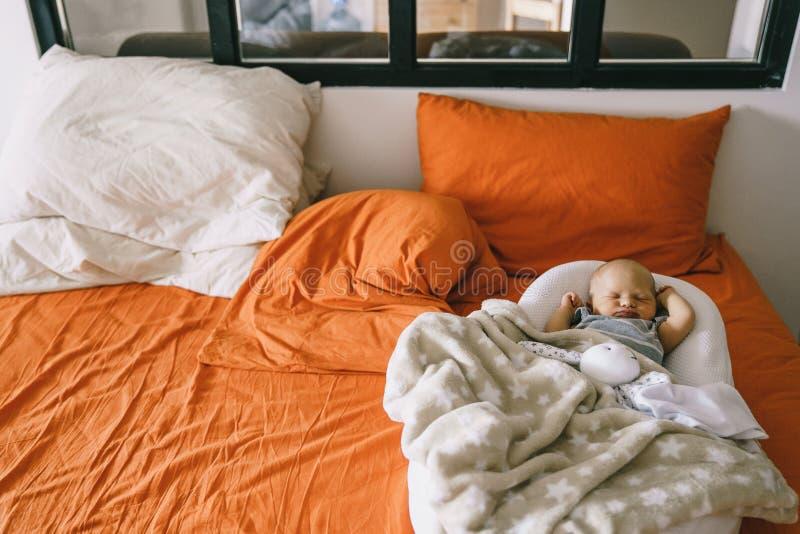 Gezonde dagslaap voor pasgeboren Een kindslaap in de orthopedische Babycocon op een groter bed in de oudersruimte royalty-vrije stock fotografie