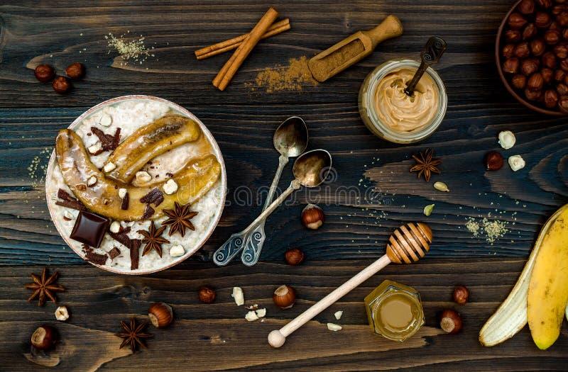 Gezonde daling en de winterontbijtkom De Chaithee goot nachtelijke die haverhavermoutpap met gekarameliseerde bananen, ruwe donke royalty-vrije stock foto's