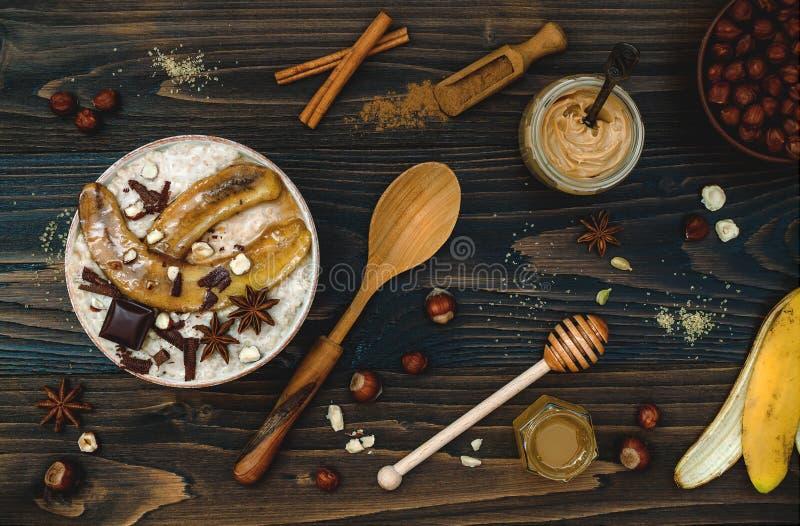 Gezonde daling en de winterontbijtkom De Chaithee goot nachtelijke die haverhavermoutpap met gekarameliseerde bananen, ruwe donke stock afbeelding