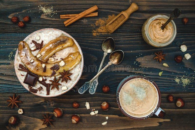 Gezonde daling en de winterontbijtkom De Chaithee goot nachtelijke die haverhavermoutpap met gekarameliseerde bananen, ruwe donke stock afbeeldingen