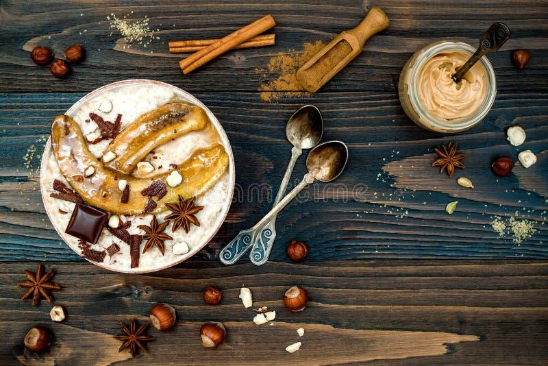 Gezonde daling en de winterontbijtkom De Chaithee goot nachtelijke die haverhavermoutpap met gekarameliseerde bananen, ruwe donke royalty-vrije stock fotografie
