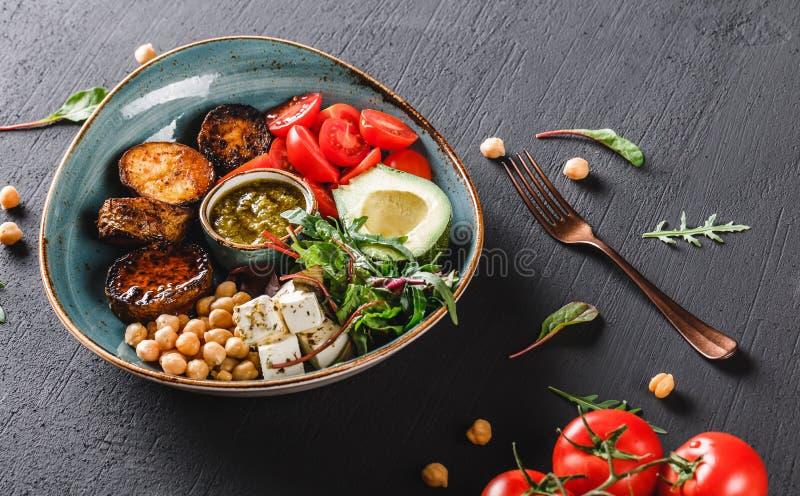 Gezonde de komschotel van Boedha met avocado, tomaat, kaas, kikkererwt, verse arugulasalade, aardappelen in de schil en sauspesto stock fotografie
