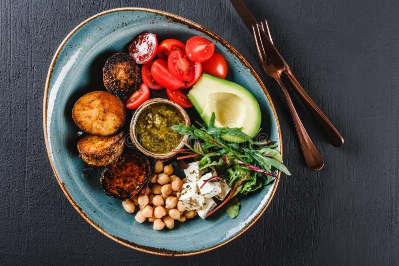 Gezonde de komschotel van Boedha met avocado, tomaat, kaas, kikkererwt, verse arugulasalade, aardappelen in de schil en sauspesto stock foto