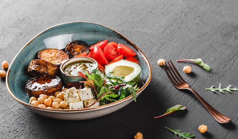 Gezonde de komschotel van Boedha met avocado, tomaat, kaas, kikkererwt, verse arugulasalade, aardappelen in de schil en sauspesto royalty-vrije stock afbeelding