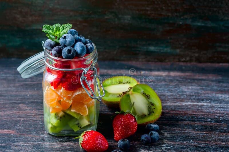 Gezonde eigengemaakte fruitsalade in een kruik op rustieke houten achtergrond Gezond voedsel, Dieet, Detox of Vegetarisch concept stock afbeelding