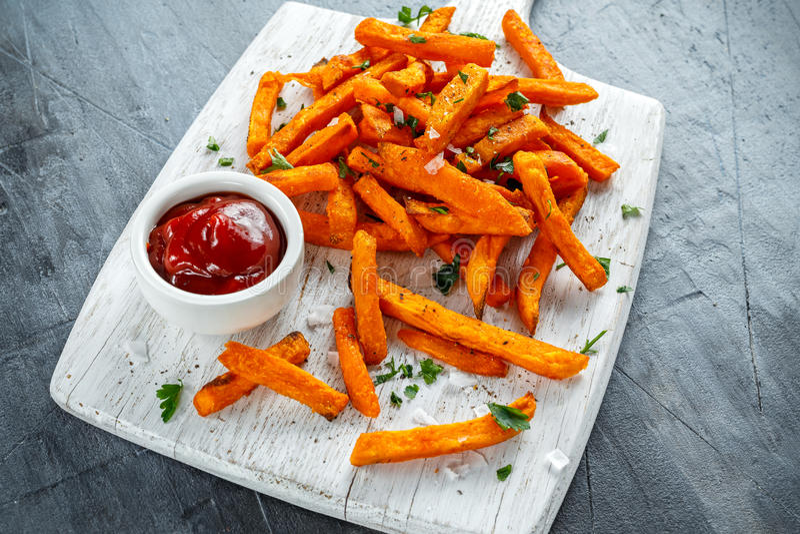 Gezonde Eigengemaakte Gebakken Oranje Bataatgebraden gerechten met ketchup, zout, peper op witte houten raad stock fotografie