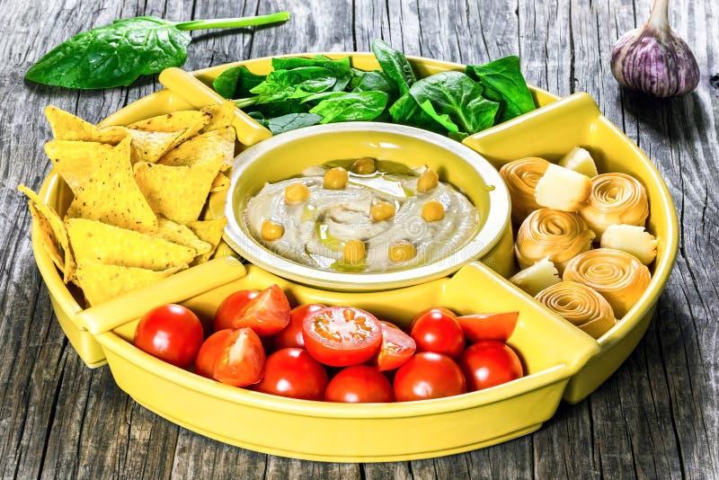Gezonde eigengemaakte heerlijke kruidige hummus met babywortelen, selderiestokken, spinazie, gember, gesneden kalk, eerste persin stock foto's