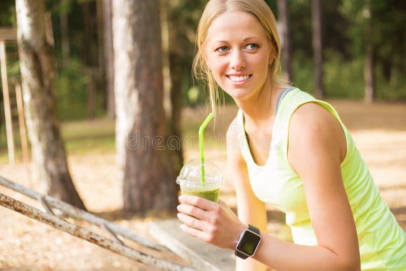 Gezonde en jonge vrouw die smoothie drinken royalty-vrije stock afbeelding