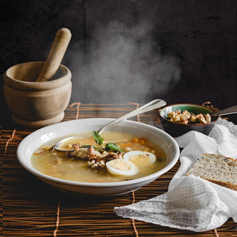 Gezonde en verwarmende de wintersoep met rijst, wortel, kekers, kip, ham en gekookt ei over rustieke achtergrond stock foto's