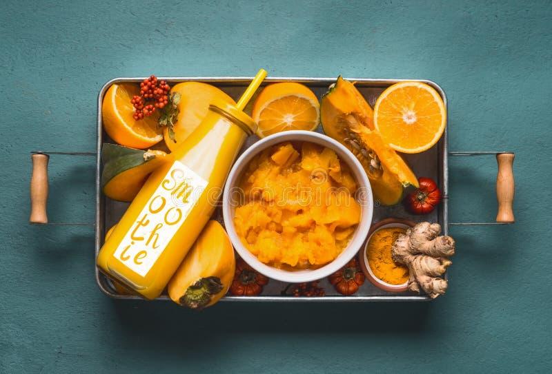 Gezonde energieke drank en woord smoothie voor koud seizoen met oranje ingrediënten: pompoen, dadelpruim, oranje vruchten, kurkum stock afbeeldingen