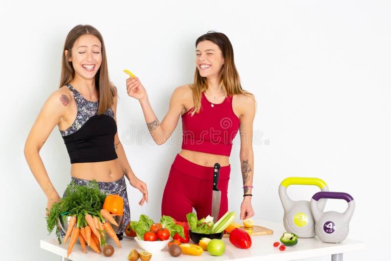 Gezonde Etende Vrouwen die Salade koken Mooie Glimlachende Veganistmeisjes die Verse Groene Organische Groenten in Keuken gaan et stock foto's