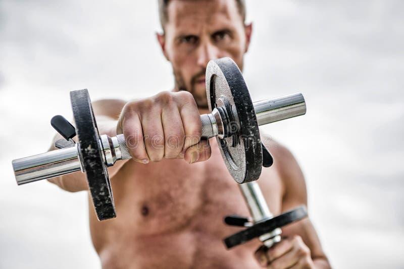 Gezonde geest in een gezond lichaam. Musculair persoon die met een dumbbels spant. Dumbbell-oefening. Dare is geweldig. Sportman stock afbeelding