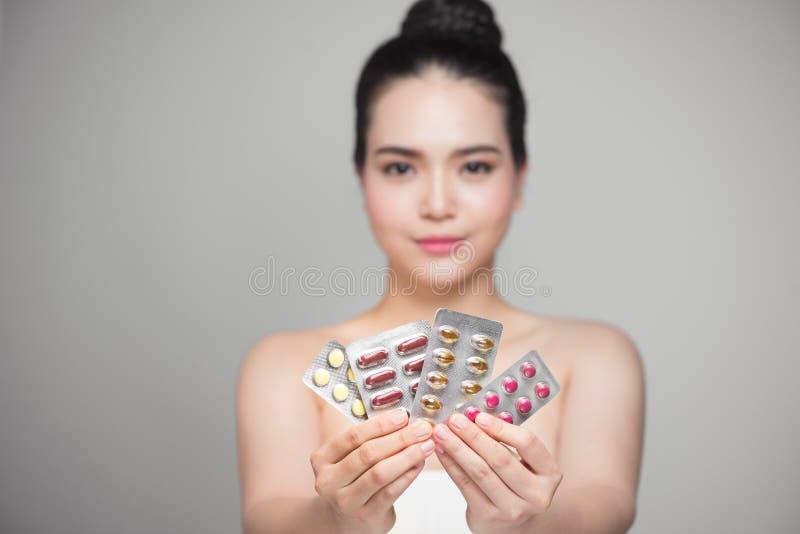 Gezonde gelukkige Aziatische vrouw met in hand pillen stock afbeeldingen