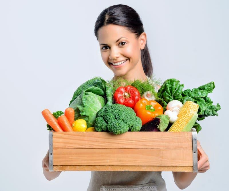 Gezonde gelukkige vrouw met krat van groenten stock afbeelding