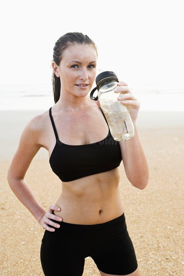 Gezonde geschikte jonge vrouw op strand drinkwater royalty-vrije stock foto