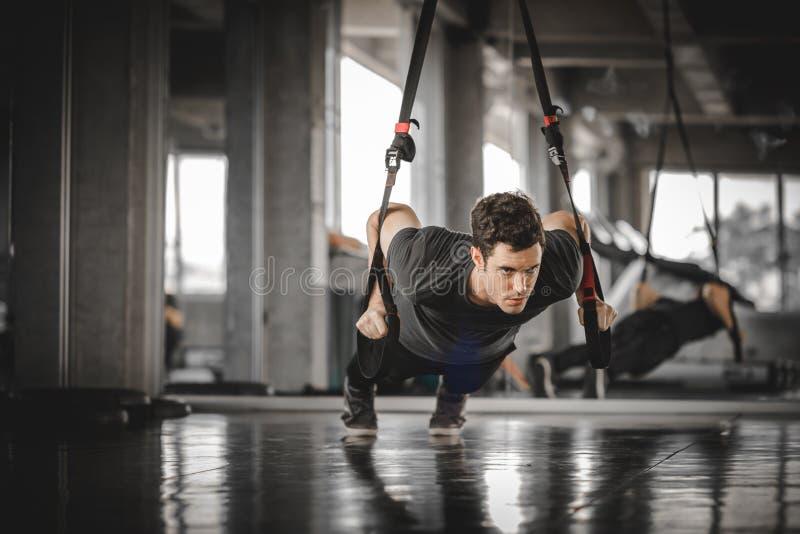 Gezonde geschiktheid die van de portret de knappe Kaukasische jonge mens duw doen omhoog bij binnentraining in gymnastiek stock fotografie
