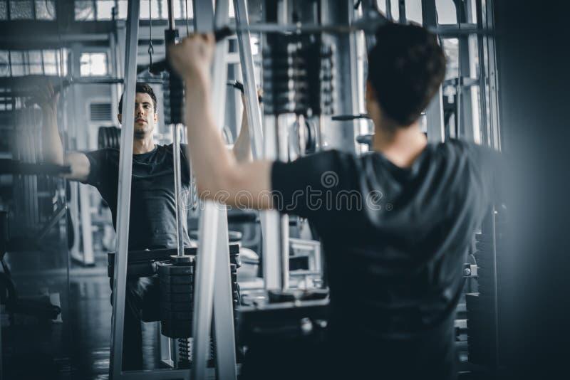 Gezonde geschiktheid die van de portret de knappe Kaukasische jonge mens oefening doen bij binnentraining in gymnastiek royalty-vrije stock fotografie
