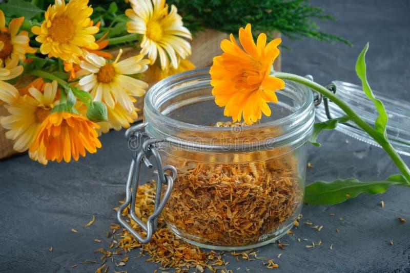 Gezonde goudsbloembloemen Geneeskrachtige kruiden in houten krat en glaskruik van droge calendulabloemblaadjes royalty-vrije stock afbeeldingen
