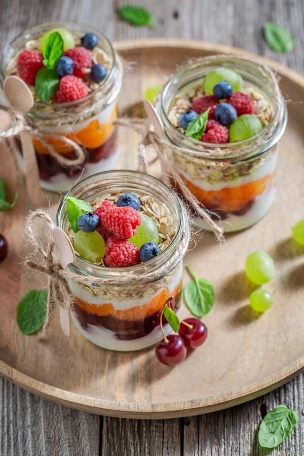 Gezonde granola in kruik met yoghurt en bessen stock afbeeldingen