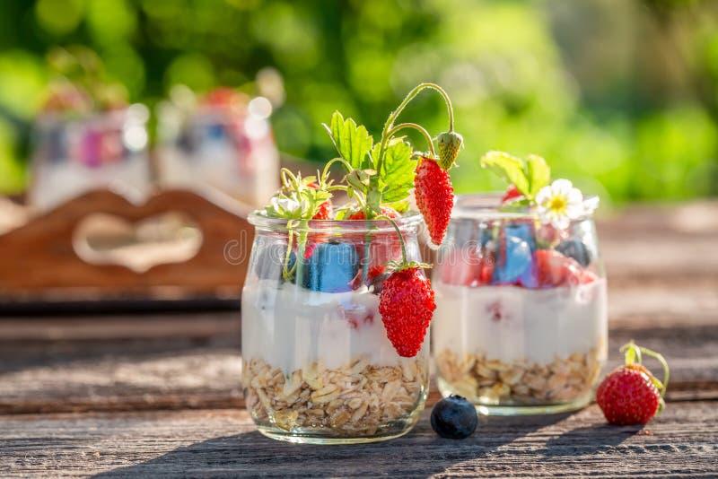 Gezonde granola in kruik met yoghurt en bessen stock foto's