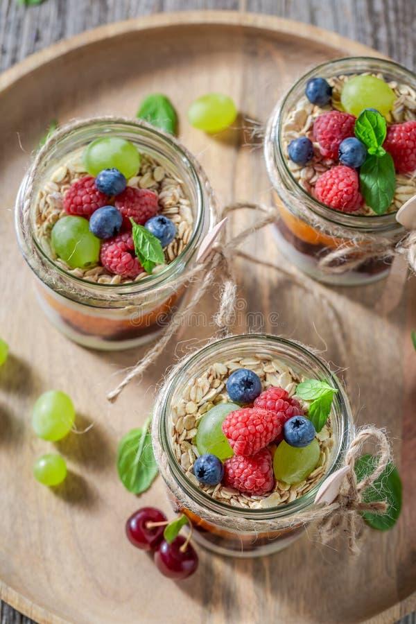 Gezonde granola in kruik met yoghurt en verse bessen stock foto's