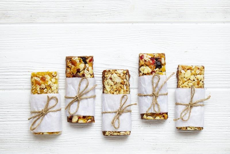 Gezonde granolabars met noten, zaden en droge vruchten op de grijze textuurlijst, met exemplaarruimte royalty-vrije stock foto