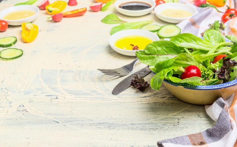 Gezonde groene saladeschotel met jonge slabladeren en diverse het kleden zich ingrediënten op lichte houten achtergrond stock fotografie
