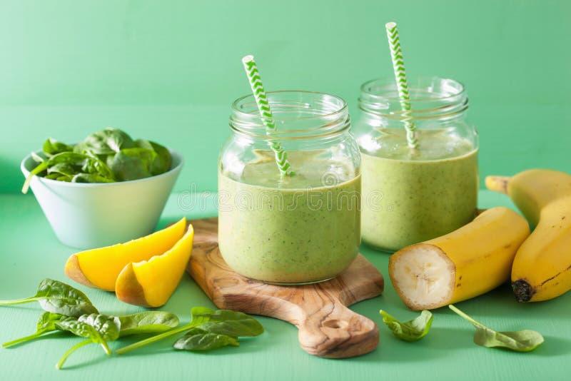 Gezonde groene smoothie met de banaan van de spinaziemango in glaskruiken stock foto