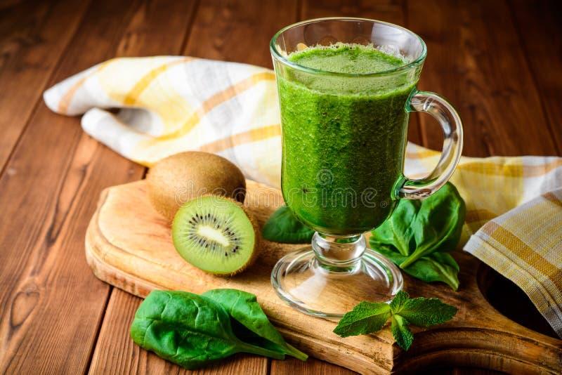 Gezonde groene smoothie met spinazie en kiwi in glas op rustieke houten achtergrond royalty-vrije stock foto's