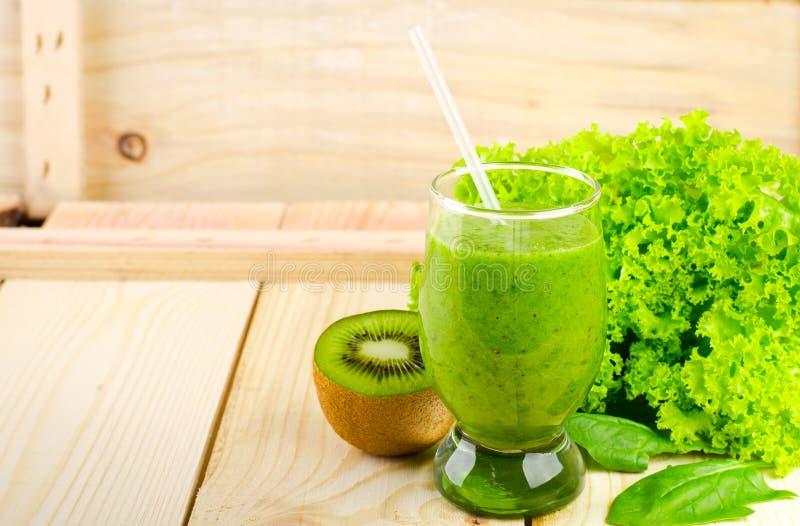 Gezonde groene smoothie met spinazie, kiwi, appelen, salade en munt in glas stock fotografie
