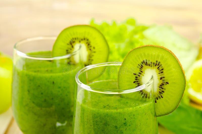 Gezonde groene smoothie met spinazie, kiwi, appelen, salade en munt in glas stock foto's