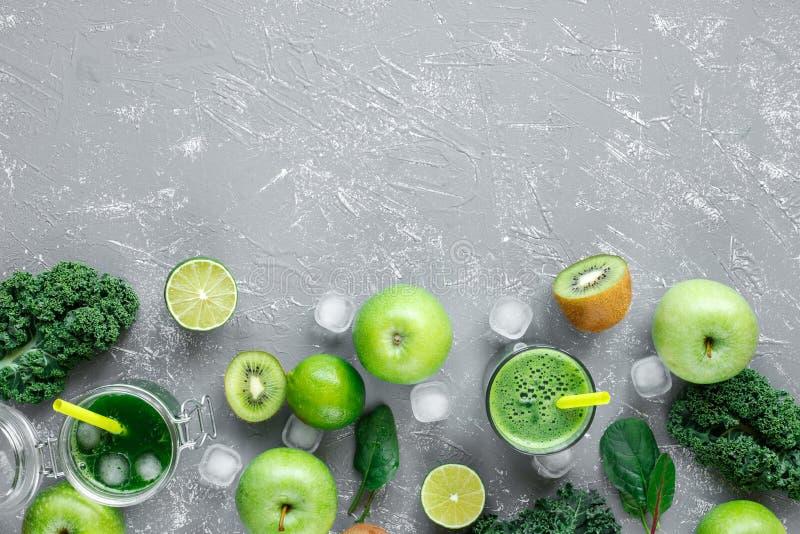 Gezonde groene smoothie met verse groene vruchten, boerenkool en spinazie op grijze achtergrond, met exemplaarruimte stock foto