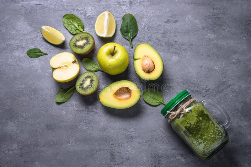 Gezonde groene smoothie in metselaarkruik en ingrediënten stock afbeeldingen