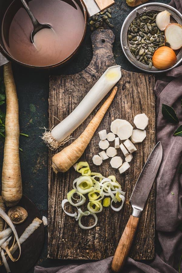 Gezonde groenten die en concept koken eten Prei en pastinaakwortelgewassen op scherpe raad met mes en pot met bouillon royalty-vrije stock afbeeldingen