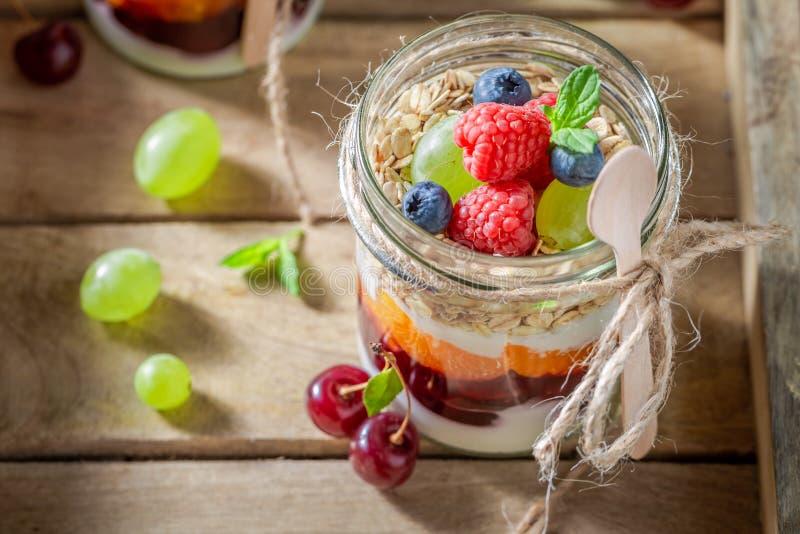Gezonde havervlokken met verse bessen en yoghurt in kruik stock afbeeldingen
