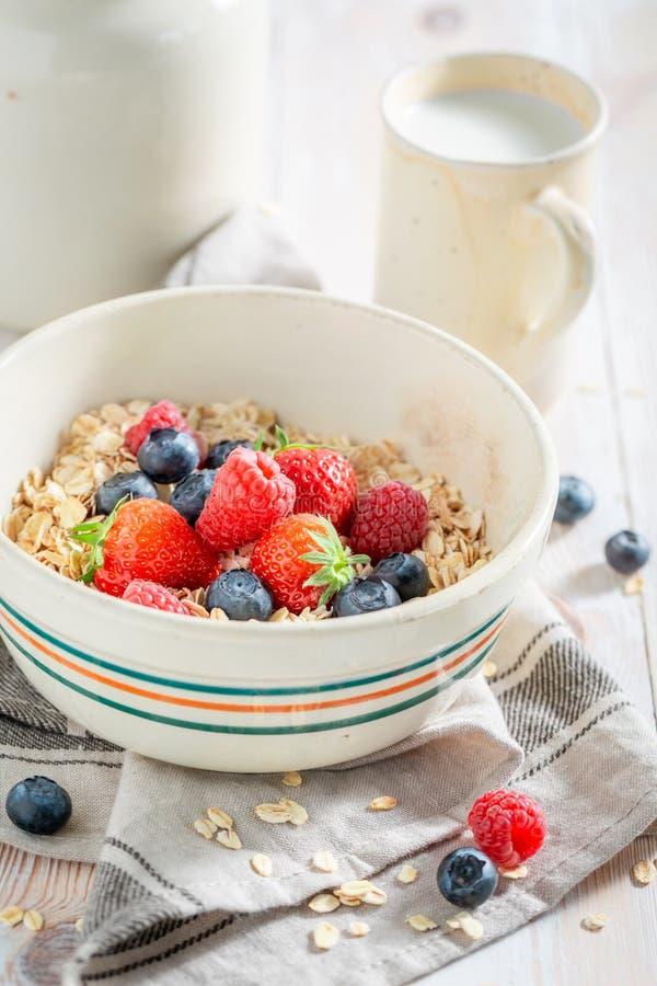 Gezonde havervlokken met vruchten voor ontbijt op witte lijst royalty-vrije stock afbeelding