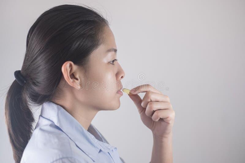 Gezonde het Eten en Dieetvoedingsconcepten Vitamine en Supplement mooie Aziatische jonge vrouw die gele vistraanpil houden stock afbeeldingen