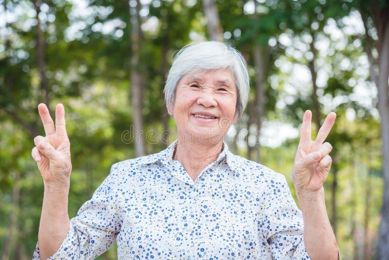 Gezonde hogere vrouw die in park glimlachen stock afbeeldingen