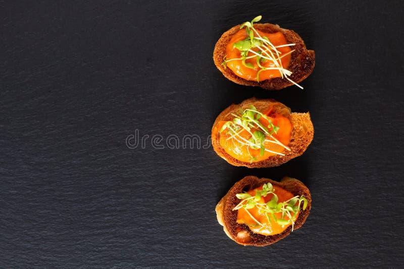 Gezonde hummus van de de veganistpompoen van het voedselconcept met vlas microgreen canapés brood op de zwarte raad van de leiste royalty-vrije stock afbeelding